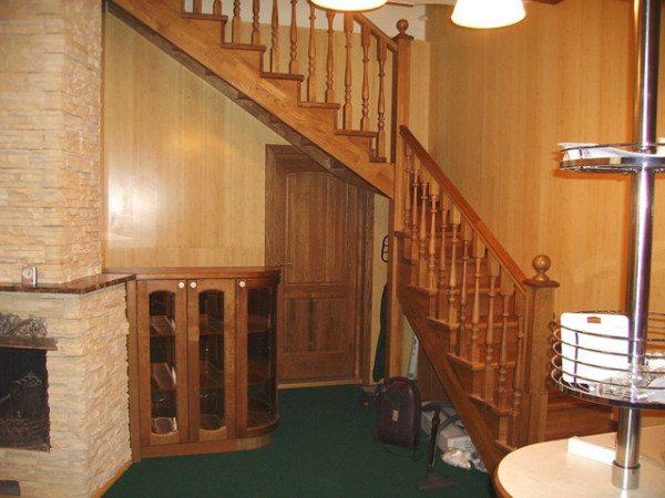 Вход в подвал под лестницей из дерева