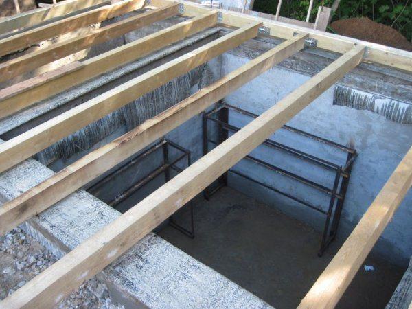 На фото – установка перекрытия погреба из деревянного бруса