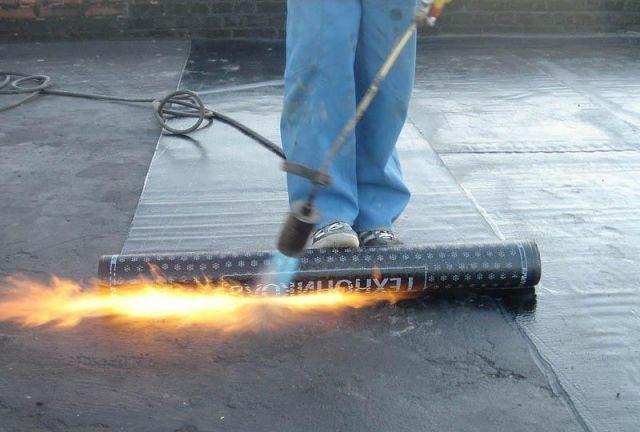 Укладка рубероида при помощи газовой горелки.